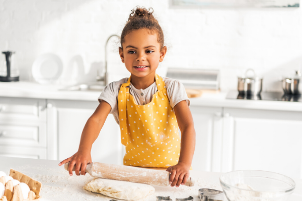 young girl rolling out bread dough