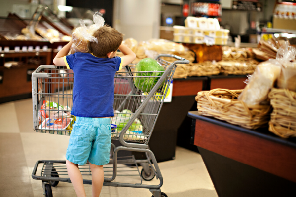 teach cooking kid putting items in grocery cart